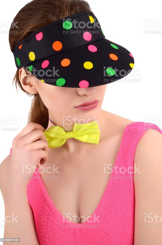 Girl with polka dots visor and bowtie looking down. stock photo