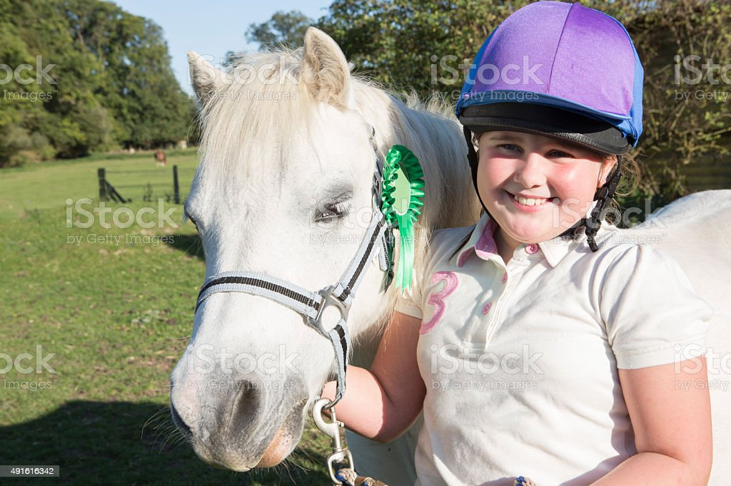 Girl With Prize Winning Pony In Field stock photo