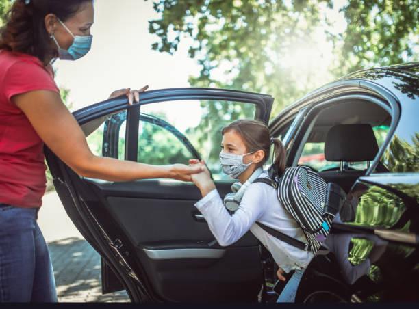 Girl with protective mask peeking through the car window