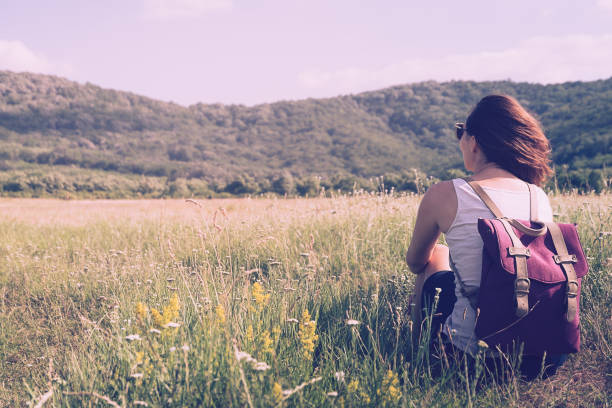 Girl with purple backpack sitting in meadow enjoying nature on summer day. stock photo