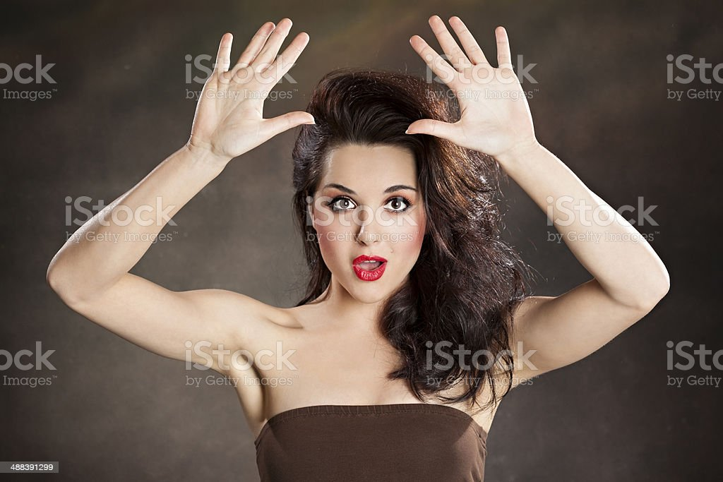 Girl with raised hands looking surprised royalty-free stock photo