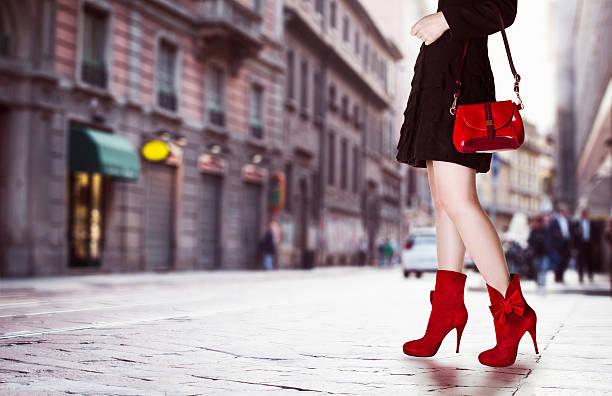 mädchen mit einer roten tasche und rote schuhe auf der straße. - schwarze hohe schuhe stock-fotos und bilder