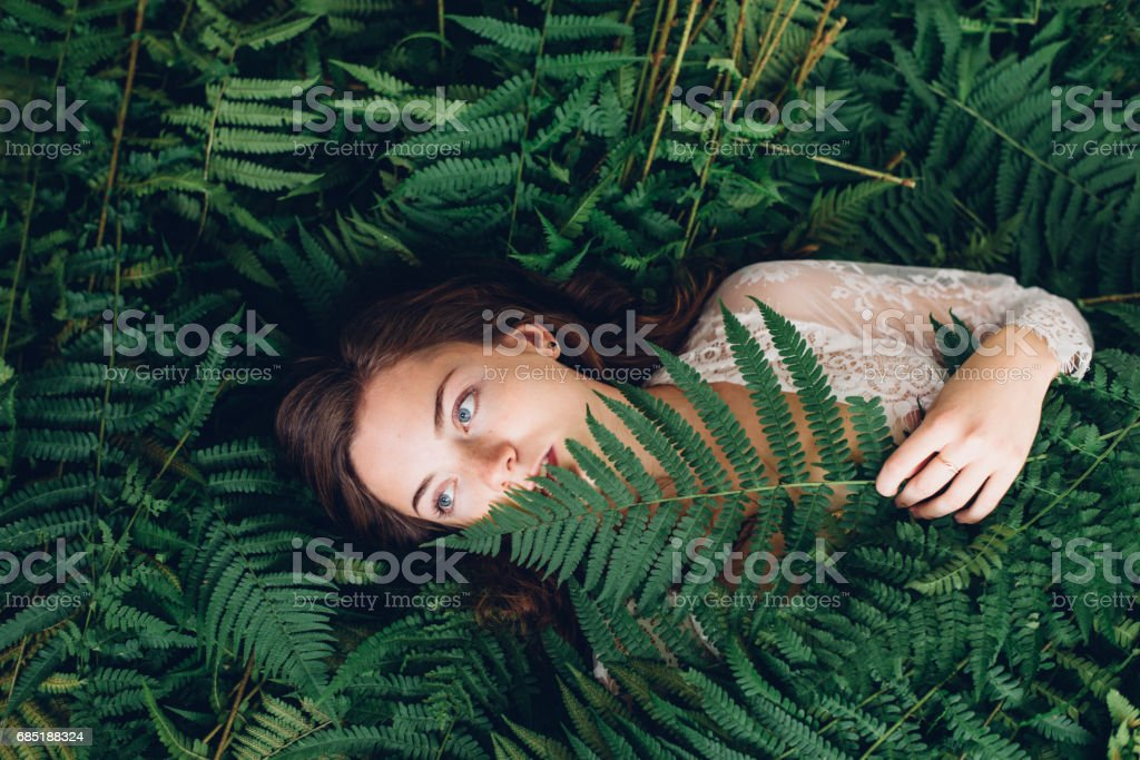 girl with red hair in an armful of ferns royalty-free stock photo