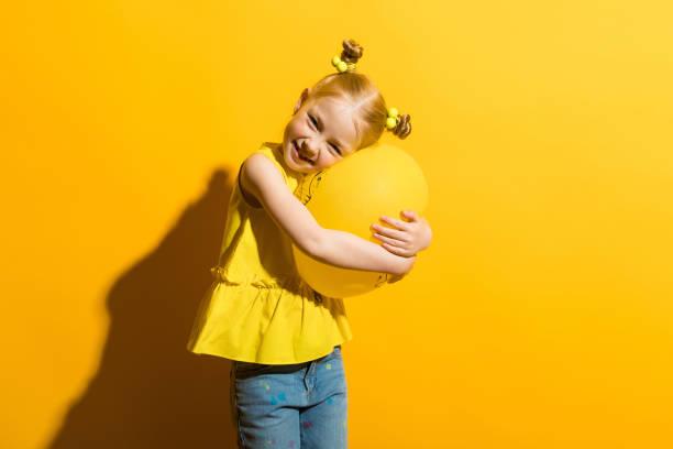 mädchen mit roten haaren auf einem gelben hintergrund. eine mädchen umarmt einen gelben ballon. - ballonhose stock-fotos und bilder