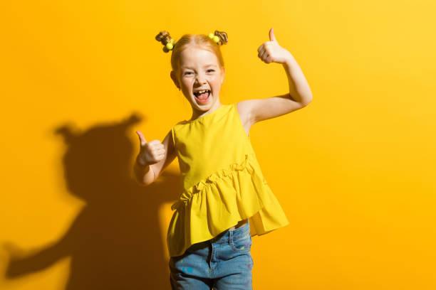 mädchen mit roten haaren auf einem gelben hintergrund. das mädchen lacht und zeigt die klasse zeichen. - schild mode stock-fotos und bilder