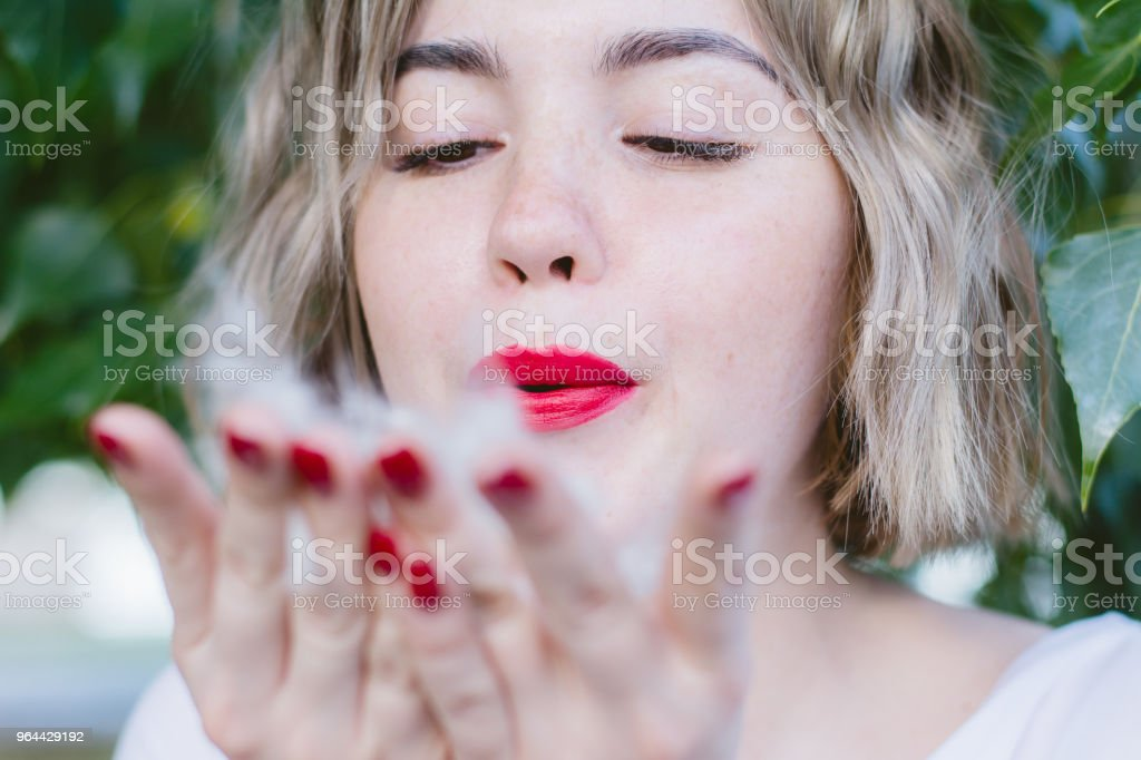Girl with red lipstick on her lips blowing on poplar fluff on her hands - Royalty-free Adult Stock Photo
