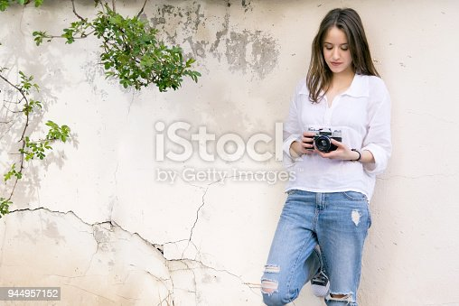 Girl with retro camera leaning against a wall. With copy space.