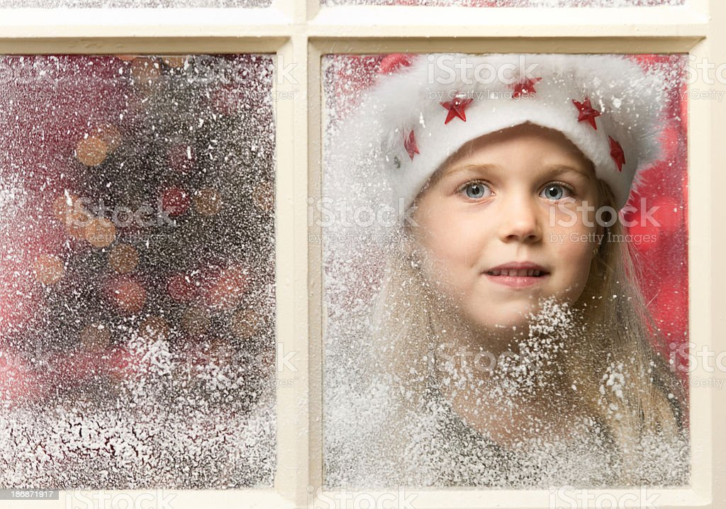 girl with Santa hat looking through snowy window at Christmas royalty-free stock photo