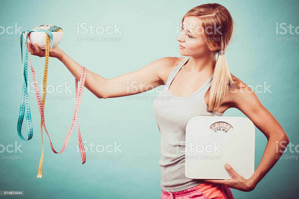 Diet, healthy eating and slim body concept. Fit fitness girl holding...