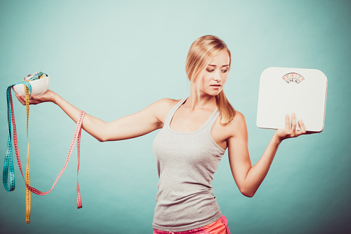 istock Girl with scales measuring tapes. Weight loss. 539462272