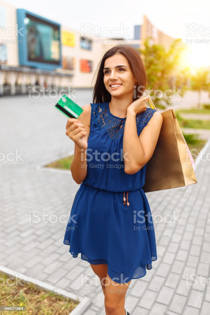 girl with shopping and card on the street, payment card