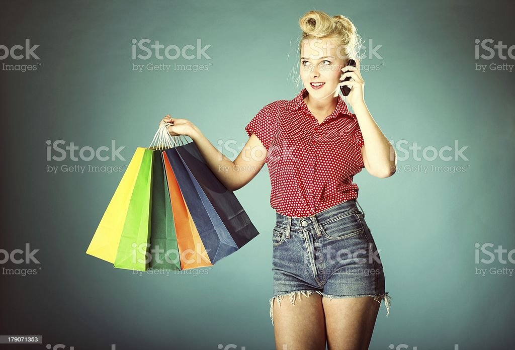 Girl with shopping bags and cell phone retro style royalty-free stock photo