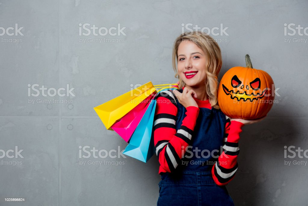girl with shopping bags and halloween pumpkin stock photo