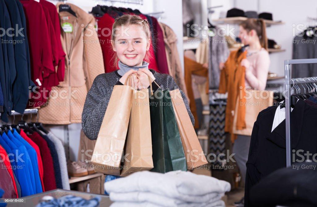女孩與母親在服裝店購物袋 - 免版稅一起圖庫照片
