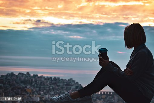Young woman looking at sunrise and drinking coffee. Silhouette.
