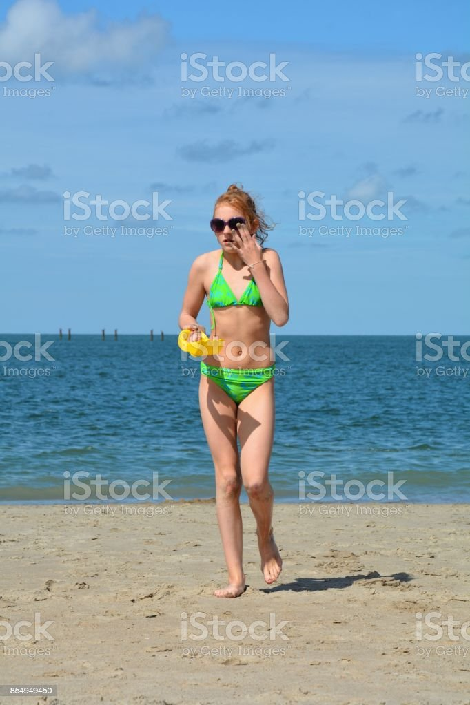 Girl with shovel in the hand runs on the beach stock photo