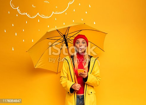 Girl with smartphone and umbrella on yellow background surprised for the rainy weather