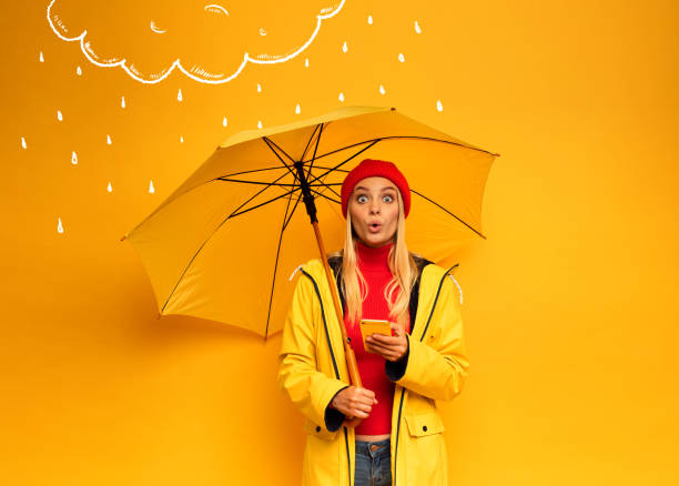 Girl with smartphone and umbrella on yellow background surprised for the weather - foto stock