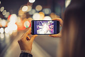 Girl using smartphone in city with beautiful bokeh