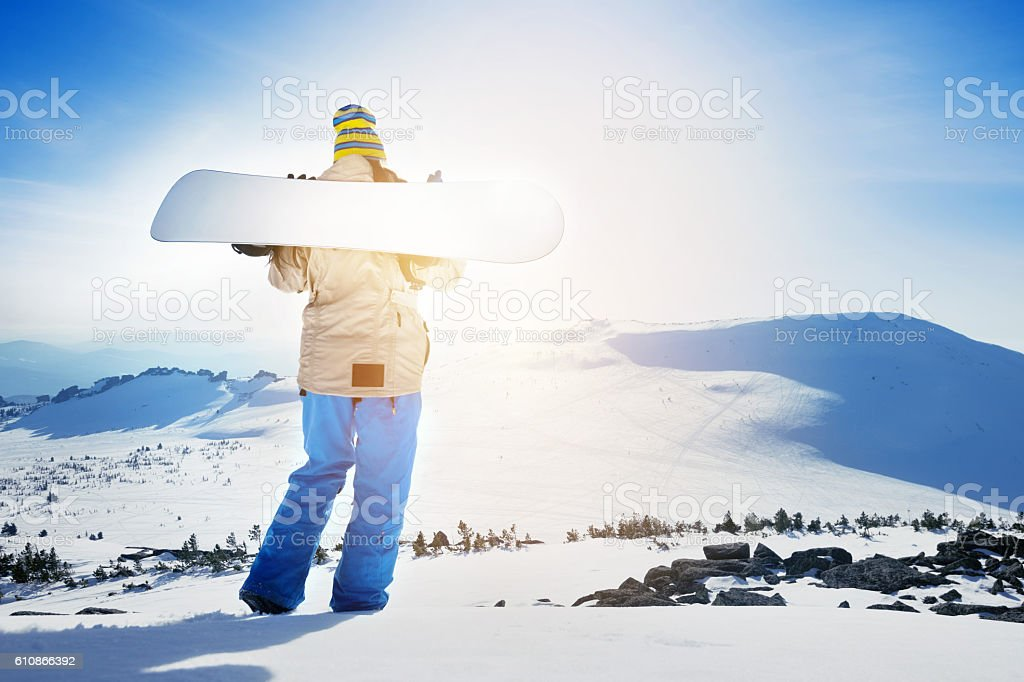 Girl with snowboard on mountain top stock photo
