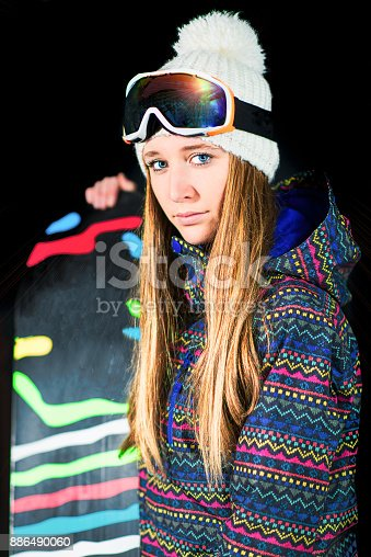 istock Girl with snowboard photographed in the studio with black background 886490060
