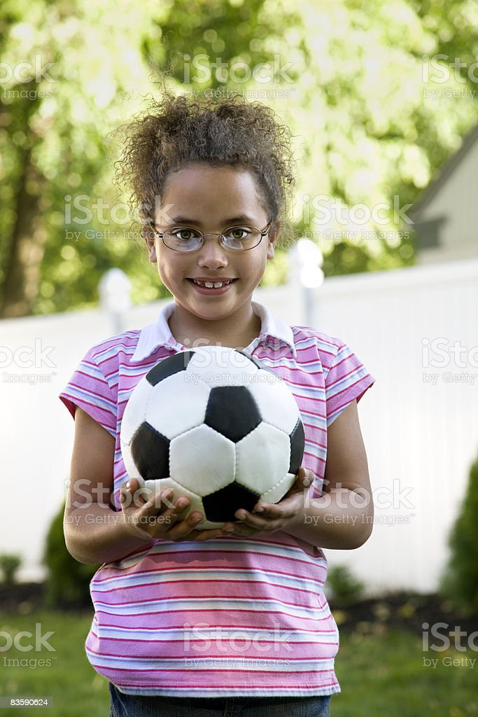 Ragazza con il pallone da calcio in cortile foto stock royalty-free