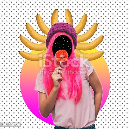 1014178170istockphoto Girl with space instead of a face and a crown of bananas eating orange candy. 964256726