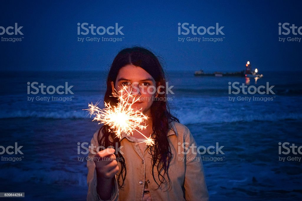 Girl with sparkler at the beach stock photo