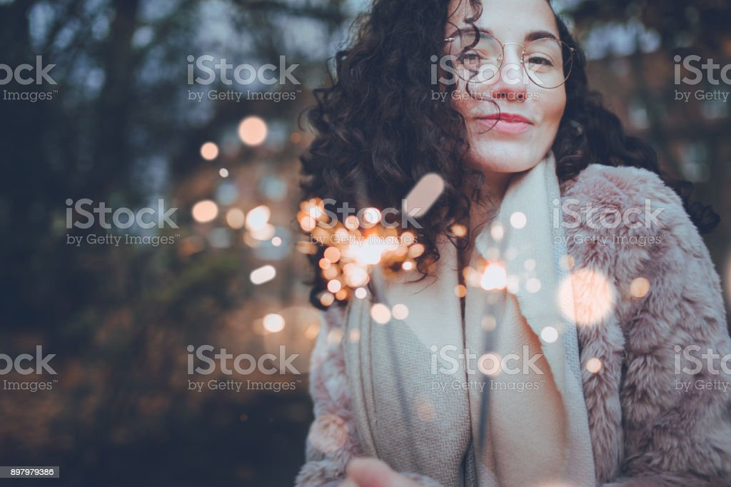 Girl with sparklers in Winter celebrating life stock photo