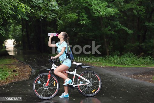 girl with sportswear stands in the park on a bicycle and drinks water