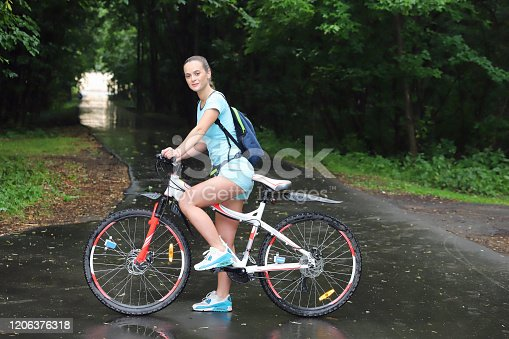 girl with sportswear stands on a bicycle in the park and looks and smiles