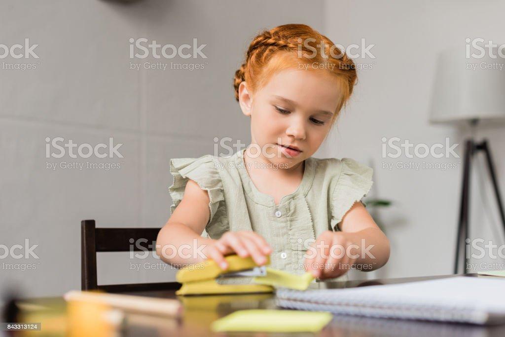 girl with stapler and paper sheet - fotografia de stock