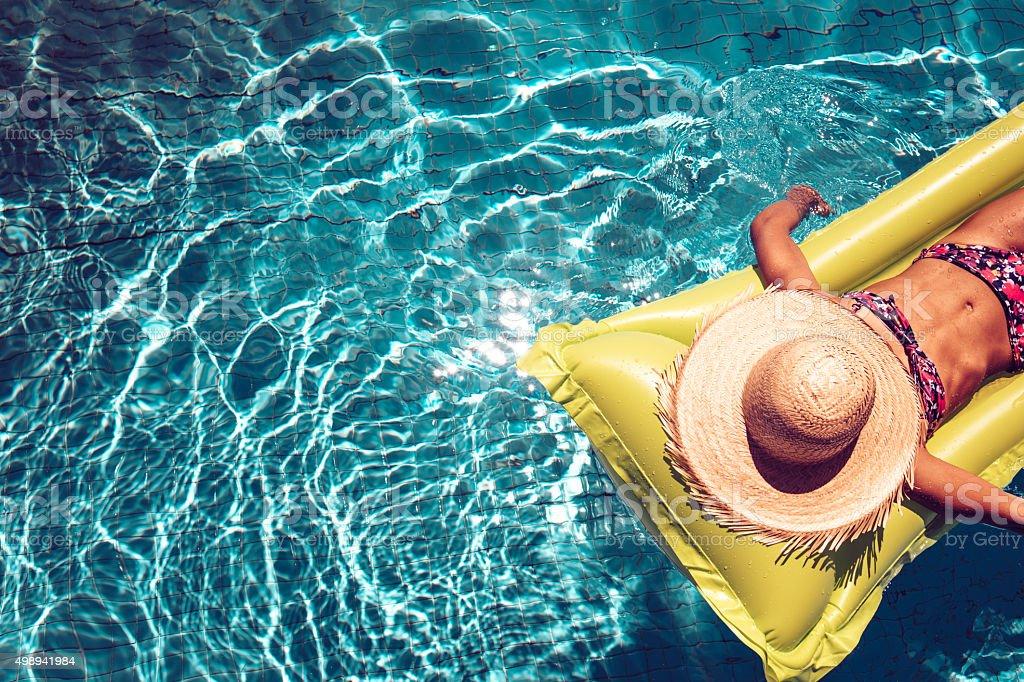 Dziewczyna z słomy kapelusz na airbed pływanie w basenie niebieski – zdjęcie