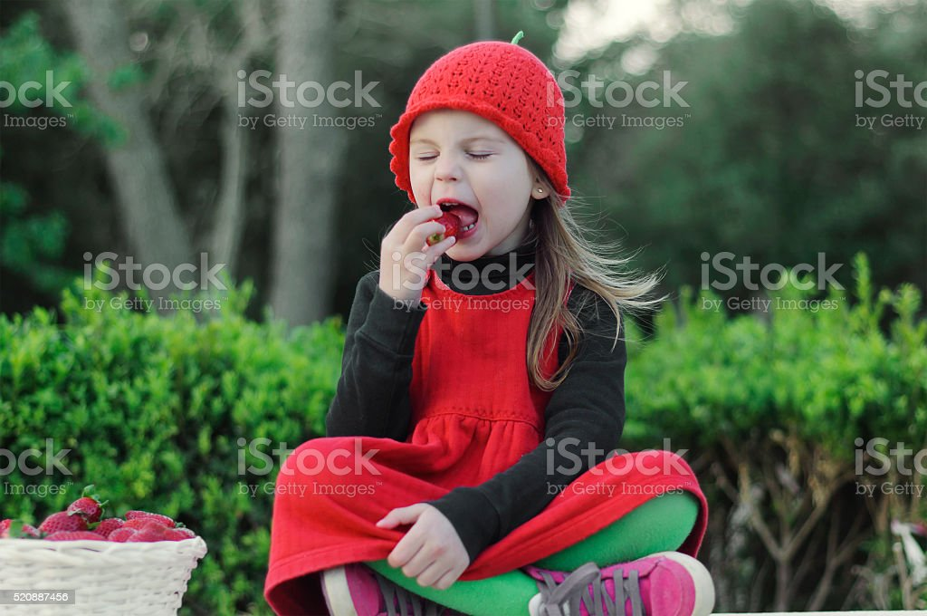 Girl with strawberries.  Girl with a red hat. stock photo