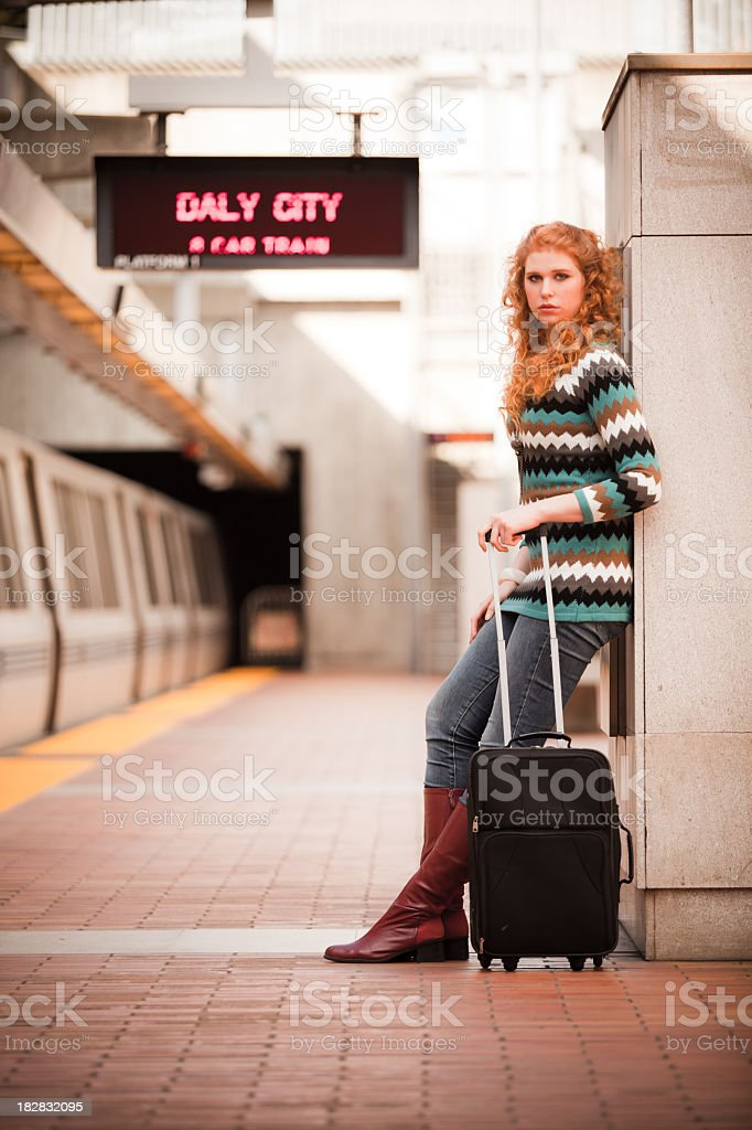 Girl with suitcase at BART station stock photo
