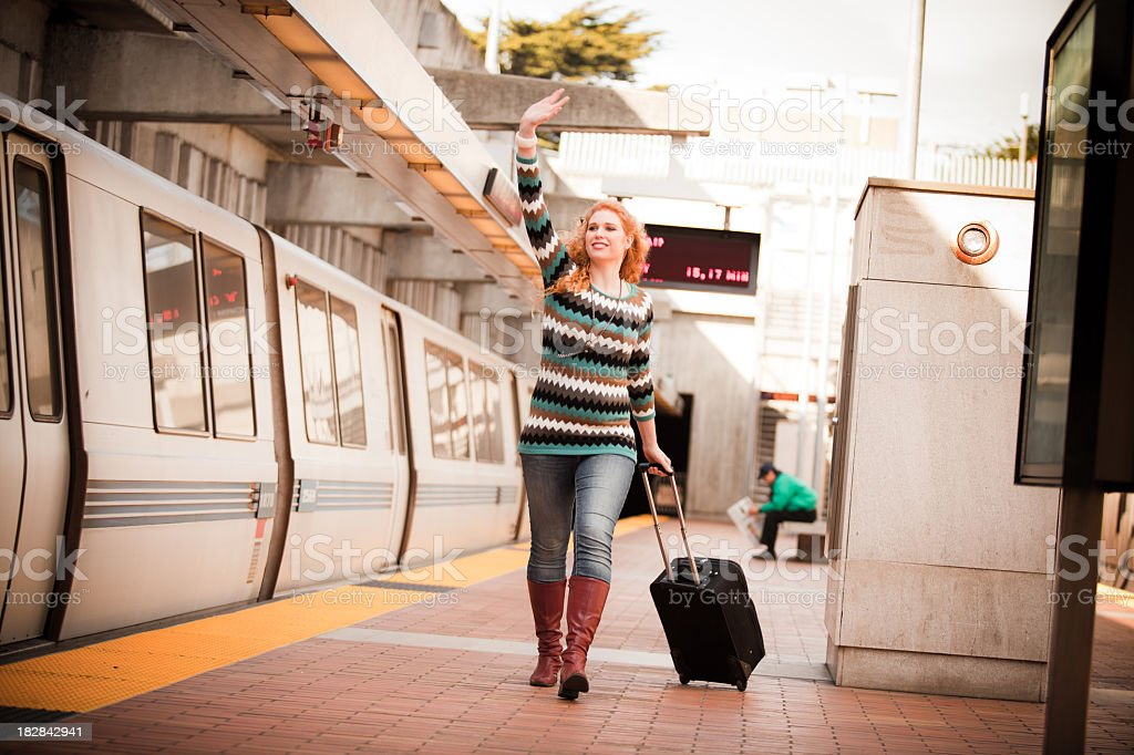 Girl with suitcase running after BART train stock photo