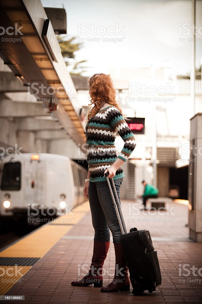 Girl with suitcase watching BART train arrive stock photo