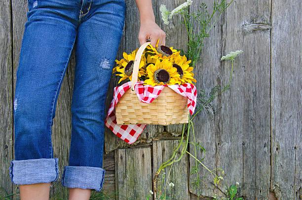 mädchen mit sonnenblume korb - denim caprihosen stock-fotos und bilder