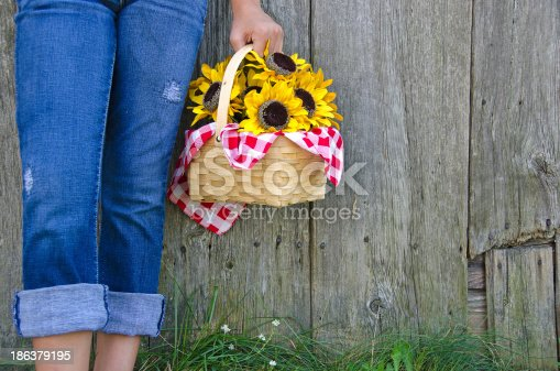 Young girl in blue jeans with basket of sunflowers.