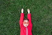 Girl with sunglasses and red jacket lies on park green grass and smile. Spending time outdoors. Child playing outside in autumn. Childhood memories. Going on journey, adventure in wilderness.