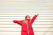 Girl with sunglasses and red jacket standing near white wall. Spending time outdoors. Child playing outside in autumn. Childhood memories. Going on journey, adventure in wilderness.