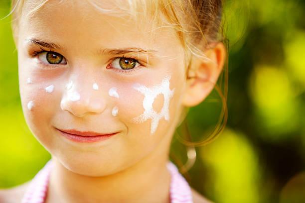 Kleines Mädchen mit Sonnencreme auf Ihr Gesicht – Foto