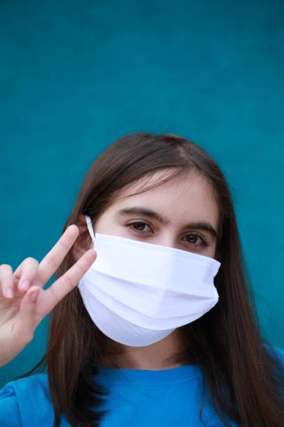 Mädchen mit chirurgischer Maske macht Siegzeichen – Foto