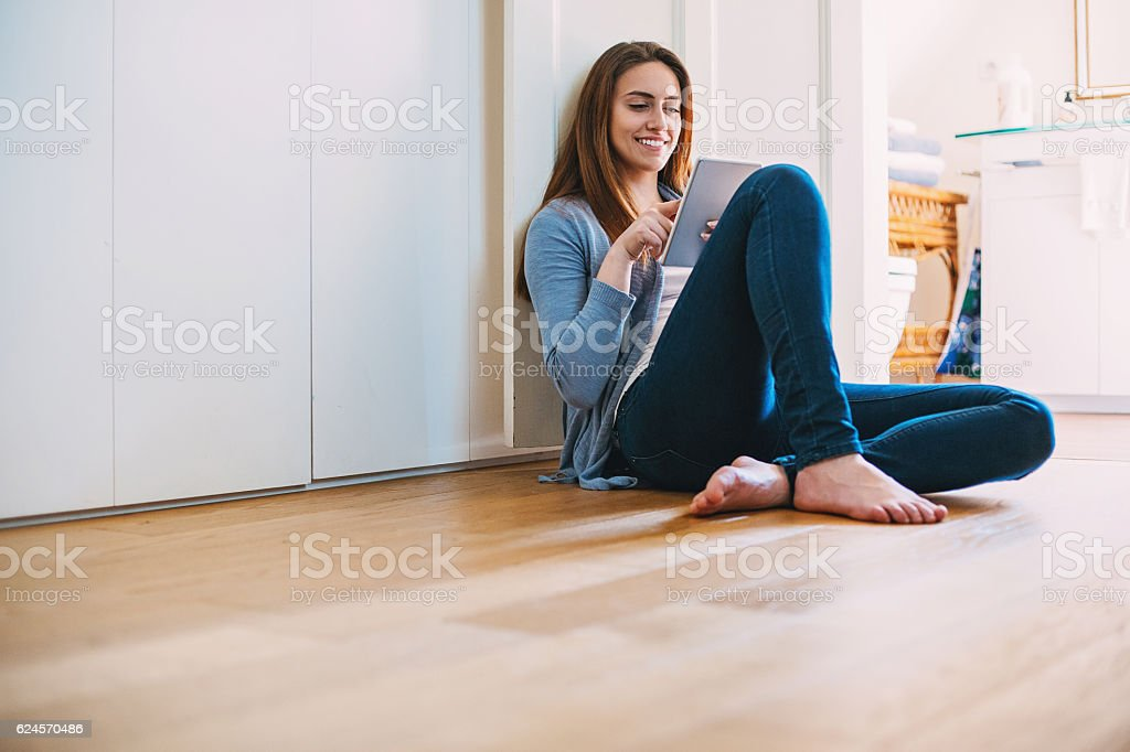 Girl with tablet sitting on the floor stock photo