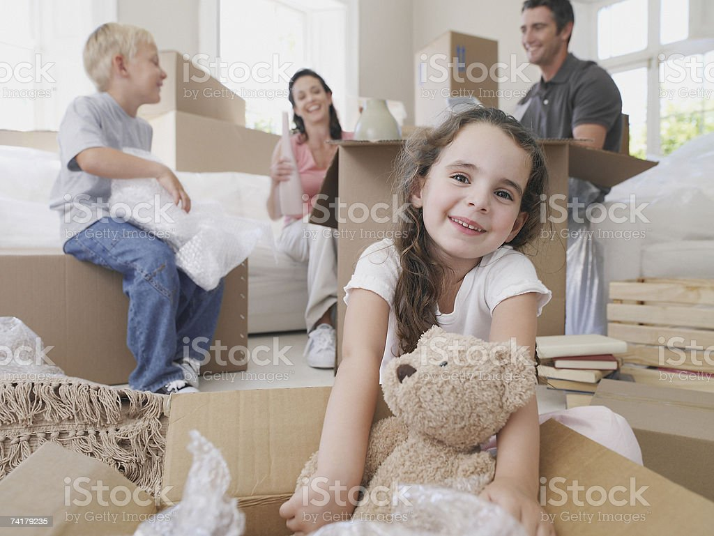 Girl with teddy bear in cardboard box with brother and parents in background stock photo