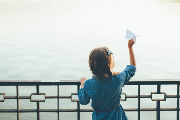 Girl with toy paper airplane looking to lake stock photo