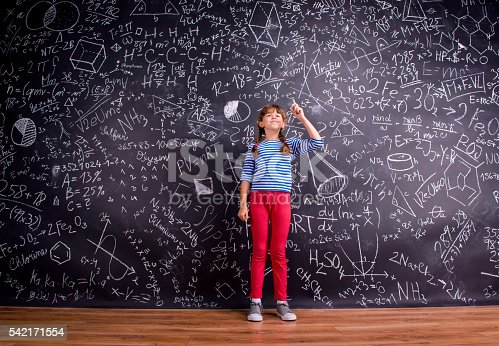 istock Girl with two braids, big blackboard with mathematical symbols 542171554