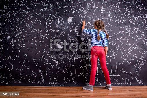 istock Girl with two braids, writing on a big blackboard 542171146