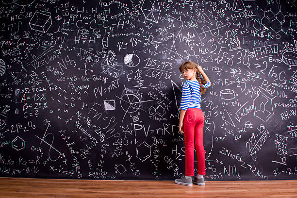 girl with two braids, writing on a big blackboard - petites filles photos et images de collection