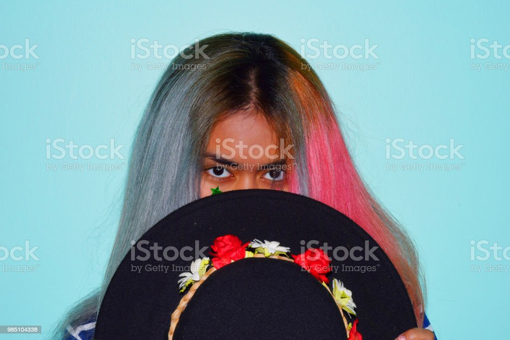 Girl With Two Hair Colors Holding Black Hat On Blue Background Stock